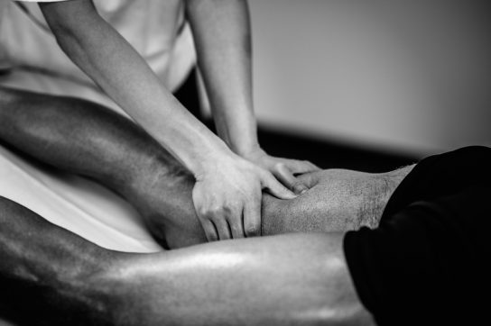 Sports massage - Leg massage - Physical therapist doing massage of legs, applying strong finger pressure. Black and white photo, selective focus.